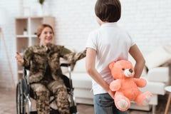Kvinnaveteran i rullstolen som hem gås tillbaka Sonen är lycklig att se hans moder, når han har gått tillbaka från armén arkivfoto