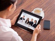 Kvinnavideoconferencing på den digitala tabellen Royaltyfri Foto