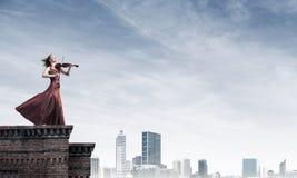 Kvinnaviolinist i den röda klänningen som spelar melodi mot molnig himmel Blandat massmedia arkivfoton