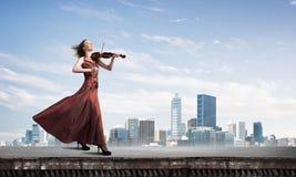 Kvinnaviolinist i den röda klänningen som spelar melodi mot molnig himmel Blandat massmedia royaltyfri foto
