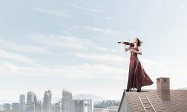 Kvinnaviolinist i den röda klänningen som spelar melodi mot molnig himmel Blandat massmedia royaltyfri bild