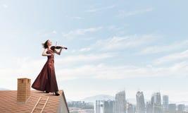 Kvinnaviolinist i den röda klänningen som spelar melodi mot molnig himmel Blandat massmedia royaltyfri illustrationer