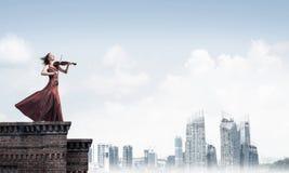 Kvinnaviolinist i den r?da kl?nningen som spelar melodi mot molnig himmel Blandat massmedia arkivbilder