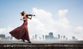 Kvinnaviolinist i den r?da kl?nningen som spelar melodi mot molnig himmel Blandat massmedia royaltyfri illustrationer