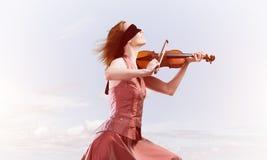 Kvinnaviolinist i den r?da kl?nningen som spelar melodi mot molnig himmel royaltyfri bild