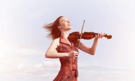Kvinnaviolinist i den r?da kl?nningen som spelar melodi mot molnig himmel arkivbilder