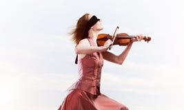 Kvinnaviolinist i den r?da kl?nningen som spelar melodi mot molnig himmel royaltyfri foto