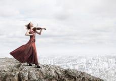Kvinnaviolinist i den r?da kl?nningen som spelar melodi mot molnig himmel arkivfoton