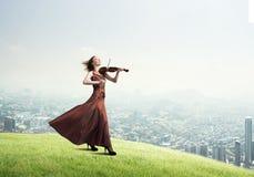 Kvinnaviolinist i den r?da kl?nningen som spelar melodi mot molnig himmel vektor illustrationer