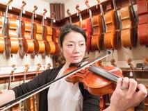 Kvinnaviolinist Playing en fiol i en Music Store Arkivfoton