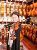 Kvinnaviolinist Playing en fiol i en Music Store Arkivfoto