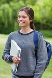Kvinnavisningen ett leende fördriver innehav en anteckningsbok Arkivfoton