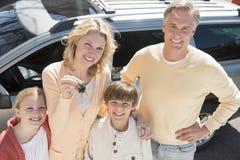 Kvinnavisningtangenter, medan stå med familjen mot bilen royaltyfria foton