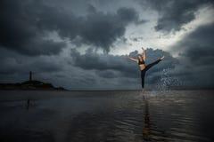 Kvinnaövning på stranden Arkivfoton