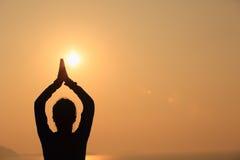 Kvinnaövningsyoga på soluppgångsjösidan Arkivfoto