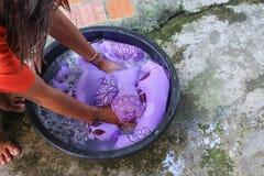 Kvinnawashhänder smutsar ner kläder i handfatsvarten för att rentvå Fotografering för Bildbyråer