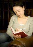 Kvinnawriting i dagbok fotografering för bildbyråer