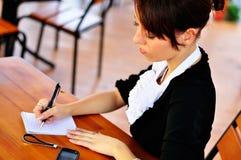 Kvinnawriting något till anteckningsboken genom att använda pennan Royaltyfri Foto