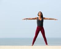 Kvinnayoga som sträcker på stranden royaltyfri foto