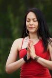 Kvinnayogin står med händer i bön Arkivbild