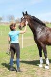 Kvinnlig ägare som skrapar halsen av hennes favorit- kastanjebruna häst arkivfoto
