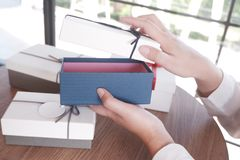 Kvinnlig öppning en gåvaask för gåvan, närvarande begrepp arkivfoton
