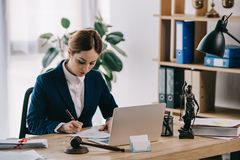 kvinnlig advokat i dräkt på arbetsplatsen med bärbara datorn, auktionsklubban och femida royaltyfria foton