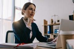 kvinnlig advokat i glasögon på arbetsplatsen med dokument och bärbara datorn arkivbild