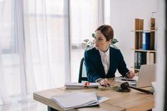 kvinnlig advokat på arbetsplatsen med mutan och bärbara datorn för auktionsklubbadollarsedlar royaltyfri bild