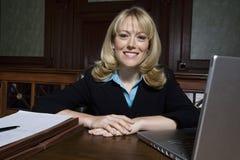 Kvinnlig advokat Sitting With Laptop och dokument Arkivbilder
