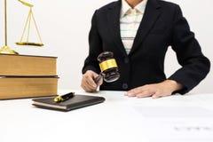 Kvinnlig advokat som i regeringsställning rymmer trämörkt rum för auktionsklubba arkivfoton