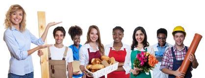 Kvinnlig affärsdeltagare i utbildning som framlägger gruppen av andra internationella lärlingar royaltyfri foto