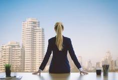 Kvinnlig affärskvinna som ut ser fönstren för framgång arkivfoton