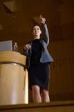 Kvinnlig affärsledare som pekar, medan ge ett anförande arkivbilder