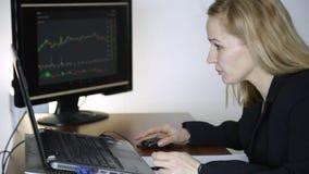 Kvinnlig affärsman som i regeringsställning arbetar på bärbara datorn Arbete på en crypto börs diagram för valutautbyte på datore stock video