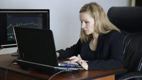 Kvinnlig affärsman som i regeringsställning arbetar på bärbara datorn Arbete på en crypto börs diagram för valutautbyte på datore lager videofilmer