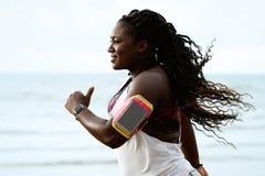 Kvinnlig afrikansk löpare som joggar under utomhus- genomkörare på stranden under regn Arkivfoton