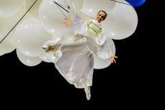 Kvinnlig akrobat inställd från ballonger Arkivbild