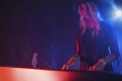 Kvinnlig aktör som spelar pianot i upplyst nattklubb Arkivbild