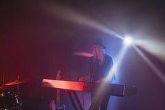 Kvinnlig aktör som spelar pianot på upplyst etapp Arkivfoton