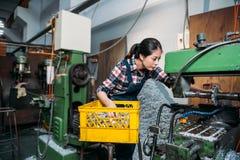 Kvinnlig anställd för malningmaskin som arbetar allvarligt Royaltyfri Foto