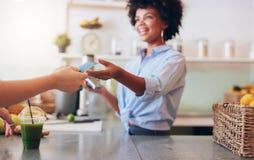 Kvinnlig anställd som tar betalning från kund Royaltyfria Foton
