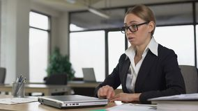 Kvinnlig anställdläsningdåliga nyheter på emailen, stängande bärbar dator angrily, avskedande lager videofilmer