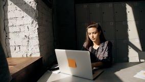 Kvinnlig användande bärbar dator och arbeta, i coworking med modern interi lager videofilmer