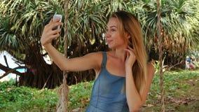 Kvinnlig användande smartphone för ultrarapidsångare som utomhus tar selfies arkivfilmer