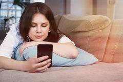 Kvinnlig anv?ndande smartphone f?r lycklig ung brunett som kopplar av p? soffan p? vardagsrum arkivfoto