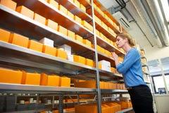 Kvinnlig apotekarbetare som söker efter medicin i lager Arkivbild