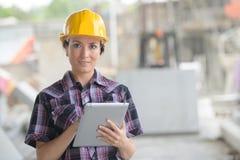 Kvinnlig arbetare i fabrik genom att använda minnestavlan arkivbilder