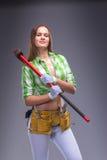 Kvinnlig arbetare i overaller som rymmer en yxa Royaltyfri Fotografi