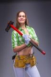 Kvinnlig arbetare i overaller som rymmer en yxa Royaltyfria Foton